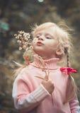 Liten blond flicka som blåser maskrosen Royaltyfria Foton