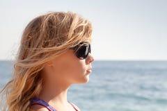 Liten blond flickaprofilstående med solglasögon royaltyfri bild