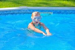 liten blond flickasimning med skyddsglasögon fotografering för bildbyråer