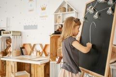 Liten blond flickateckning på svart tavla i hennes vita rum I arkivbild
