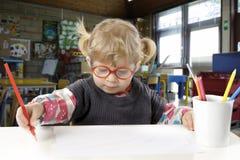 Liten blond litet barnflicka som gör en teckning Fotografering för Bildbyråer