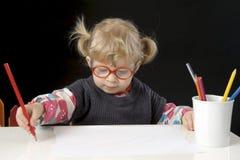 Liten blond litet barnflicka som gör en teckning Royaltyfri Fotografi