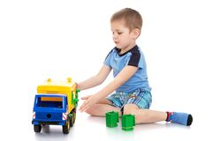 Liten blond pojke i en blå t-skjorta och kortslutningar Royaltyfri Bild