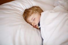 Liten blond pojke som sover i hans säng Arkivfoton