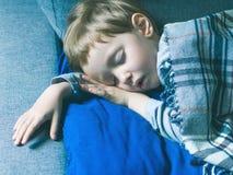 Liten blond pojke som sover under en filt arkivbild