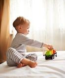 Liten blond pojke som spelar med bilen Arkivfoton