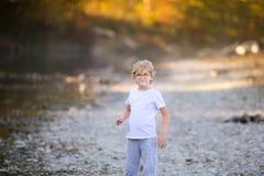 Liten blond pojke som spelar på flodstranden Höst i den gula skogen Fotografering för Bildbyråer