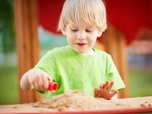 Liten blond pojke som spelar på lekplats Royaltyfri Fotografi
