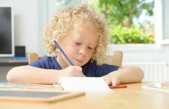 Liten blond pojketeckning i hans hem Fotografering för Bildbyråer