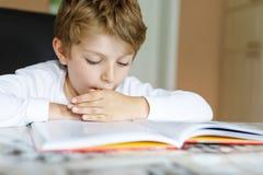 Liten blond skolaungepojke som hemma läser en bok Barn som intresseras i den läs- tidskriften för ungar Fritid för ungar arkivbilder