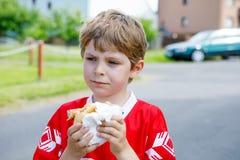 Liten blond ungepojke som äter varmkorven, når att ha spelat fotboll Arkivbilder