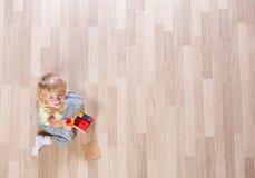 Liten blond ungepojke som spelar med färgrika byggnadskvarter på bästa sikt för golv fotografering för bildbyråer