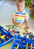 Liten blond ungepojke som spelar med massor av färgrikt plast- kvarter Royaltyfri Bild