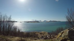 Liten bosättning på havsöar med snöig berg och solsken på klara blått stock video