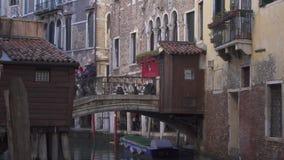 Liten bro på en kanal i Venedig med folk och historiska byggnader stock video