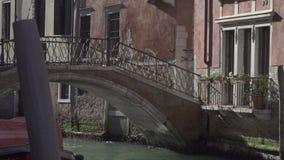 Liten bro på en kanal i Venedig med historiska byggnader lager videofilmer