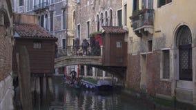 Liten bro p? en kanal i Venedig med folk och historiska byggnader stock video