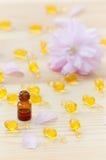 Liten brun flaska med nödvändiga oljor för ros, guld- kapslar av den naturliga skönhetsmedlet och den körsbärsröda blomningen på  Arkivfoton