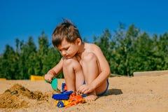Liten brunbränd pojke som spelar på en sandig strand royaltyfri bild