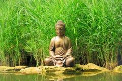 Liten Buddha nära dammet Royaltyfria Bilder