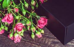 Liten bukett av rosor och gåvan på en träbakgrund royaltyfria bilder