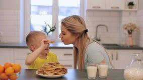 Liten caucasian blond pojke som har gyckel med den unga mamman Pojke som retar mammapannkakor lyckligt ha för frukostfamilj tills arkivfilmer