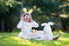 Liten Caucasian flicka i festlig klänning och kaninörahuvudbindeln som sitter på grönt gräs och spelar med påskägg och flott stor fotografering för bildbyråer