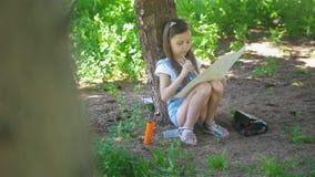Liten caucasian flickateckning med borstesammanträde under trädet på sommar arkivfilmer