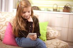 Liten Caucasian flickatext hennes vänner på socialt nätverk Fotografering för Bildbyråer
