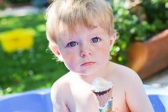 Liten caucasian litet barnpojke som äter glass i kotte Arkivbild