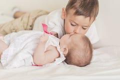 Liten Caucasian pojke som kysser hans nyfödda syster Sköt inomhus Royaltyfri Foto