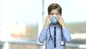 Liten caucasian pojke som spelar en doktor stock video