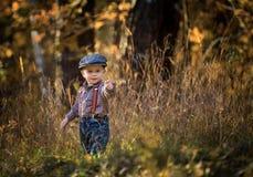 Liten caucasian pojke som spelar i vårlandskap arkivfoto