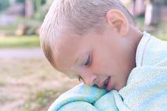 Liten Caucasian pojke som värma sig efter bad i sjön Pojken täckte sig med handduken och sitter på kusten av Royaltyfri Fotografi