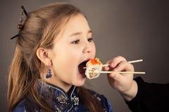 Liten charmig flicka som äter rulle arkivfoto