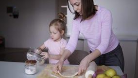 Liten cutieflicka som hjälper hennes moder på köket som förbereder deg för kakorna Ung kvinna som rullar på degen lager videofilmer