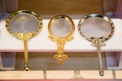Liten dekorativ guld- färghandspegel Fotografering för Bildbyråer