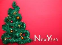 Liten dekorerad julgran med text för LYCKLIGT NYTT ÅR på väggen Fotografering för Bildbyråer