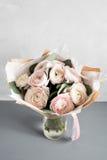Liten delikat elegant bukett av blommor, smörblommor och eukalyptuns i tenn- can och en tekopp på vitgrå färgtabellen royaltyfria bilder
