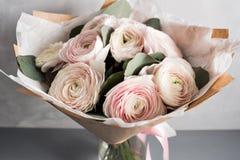 Liten delikat elegant bukett av blommor, smörblommor och eukalyptuns i tenn- can och en tekopp på vitgrå färgtabellen royaltyfri foto