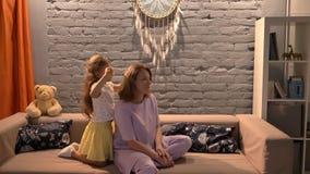 Liten dotter som borstar hennes moderhår med hårborsten som inomhus sitter på soffan i modern vardagsrum, familjbegrepp arkivfilmer