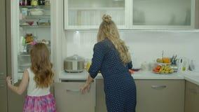 Liten dotter som hjälper hennes mamma att laga mat i kök stock video