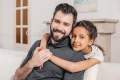 Liten dotter som kramar le fadern, mångkulturell familj hemma Royaltyfria Foton