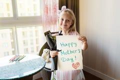 Liten dotter som rymmer den m?lade vykortet och buketten av blommor f?r mamma Lyckligt mors dagbegrepp royaltyfri bild