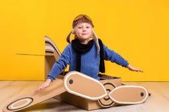 Liten drömmareflicka som spelar med ett pappflygplan Barndom Fantasi fantasi Fotografering för Bildbyråer