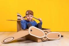 Liten drömmareflicka som spelar med ett pappflygplan Barndom Fantasi fantasi Arkivbild