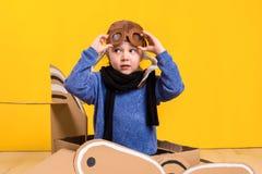 Liten drömmareflicka som spelar med ett pappflygplan Barndom Fantasi fantasi Arkivbilder