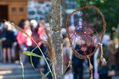 Liten dreamcatcher hänger i ett träd framme av en folkmassa arkivfoton