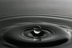 Liten droppe av vatten från en färgstänk Arkivfoton