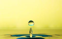 Liten droppe av vatten från en färgstänk Arkivbilder